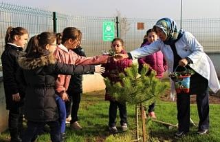Minik eller çapa kürekle çalışarak okul bahçesini...
